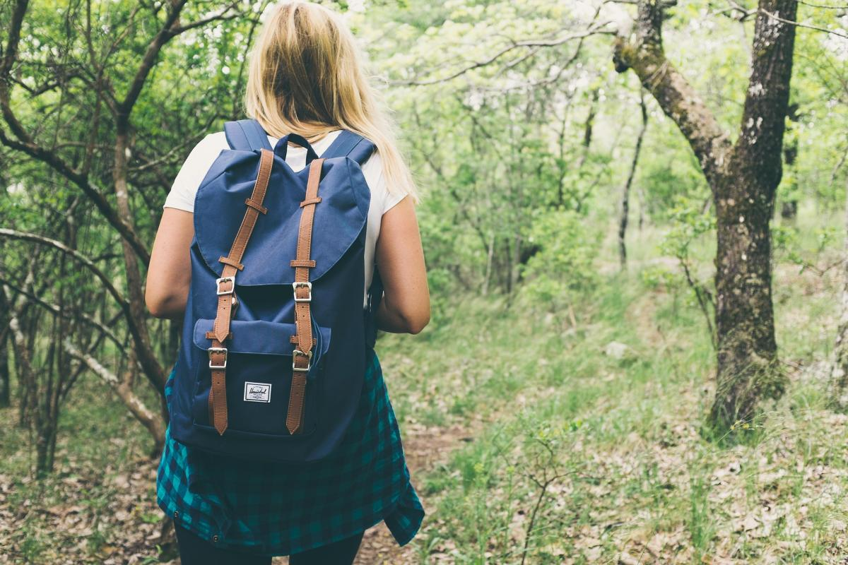Woman with a backpack hiking in woods