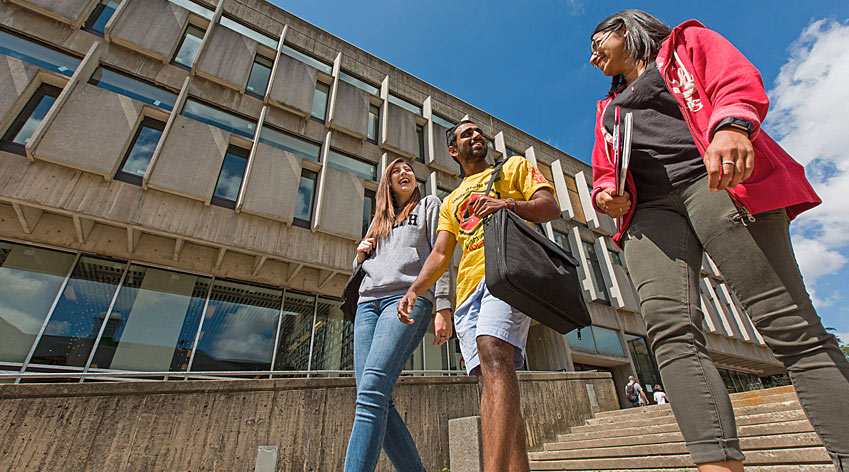 Students walking past campus buildings.