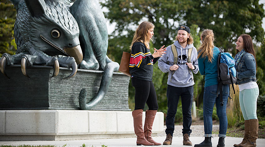 Students standing in front of the Gryphon statue.